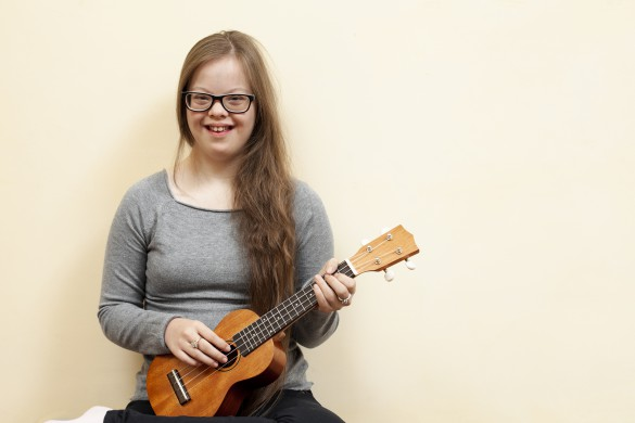 smiley-girl-with-down-syndrome-holding-guitar